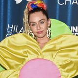 Was wäre ein Auftritt von Miley Cyrus ohne ein sonderbares Outfit? Im zweifelhaften Blumenkleid und mit gigantischen Ohrringen und Dreadlocks besucht die Sängerin ein Charity-Event.
