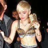 Was, ja was hat sich Miley Cyrus bei diesem Outfit gedacht? Liz-Hurley-Gedächtnis-Nadeln an der Strumpfhose, prollige Unterwäsche von Versace Versus, Holzfällerhemd und Tanzkurs-Treter ergeben zusammen ein Outfit, ähnlich schrecklich wie der Gesichtsausdruck ihres Begleiters.
