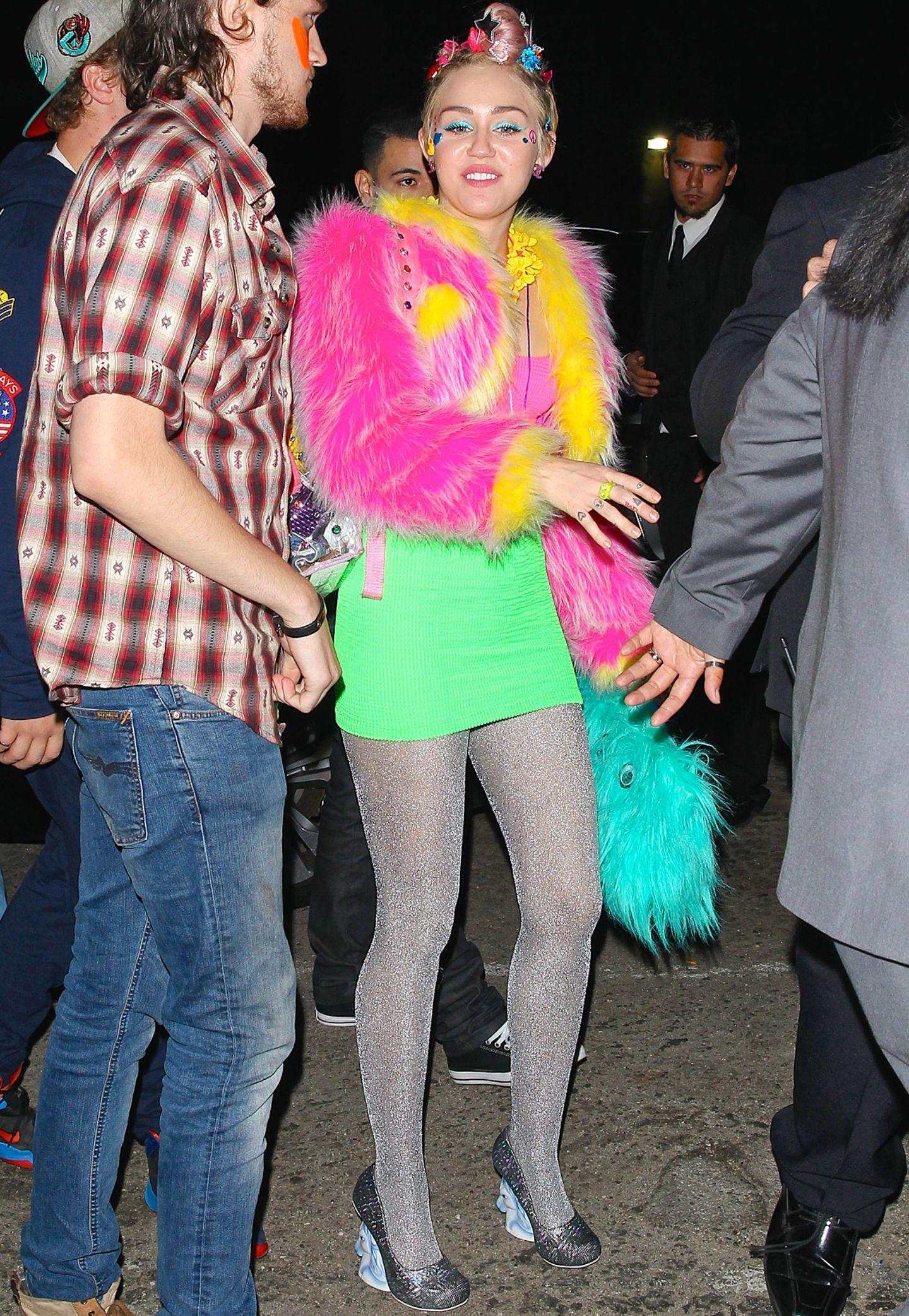 """Damit keiner ihrer Gäste sie auf ihrer Party zum 22. Geburtstag verfehlen kann, hat sich Miley Cyrus besonders schrill angezogen. Frei nach dem Motto """"Hauptsache Neon und Glitzer"""" kombiniert die Sängerin eine bunt leuchtende Fake-Fur-Jacke zu Minirock und Metallic-Strumpfhose."""
