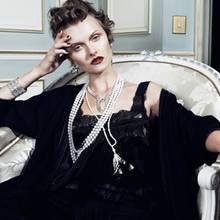 Mehrreihige Perlenkette und Diamantohrringe mit Onyx, von Chanel Fine Jewelry. Perlenkette mit Quaste, von Tiffany & Co. Diamant-Collier und -Armbänder von Boucheron. Lingerie von La Perla. Kaschmirmantel von Hermès