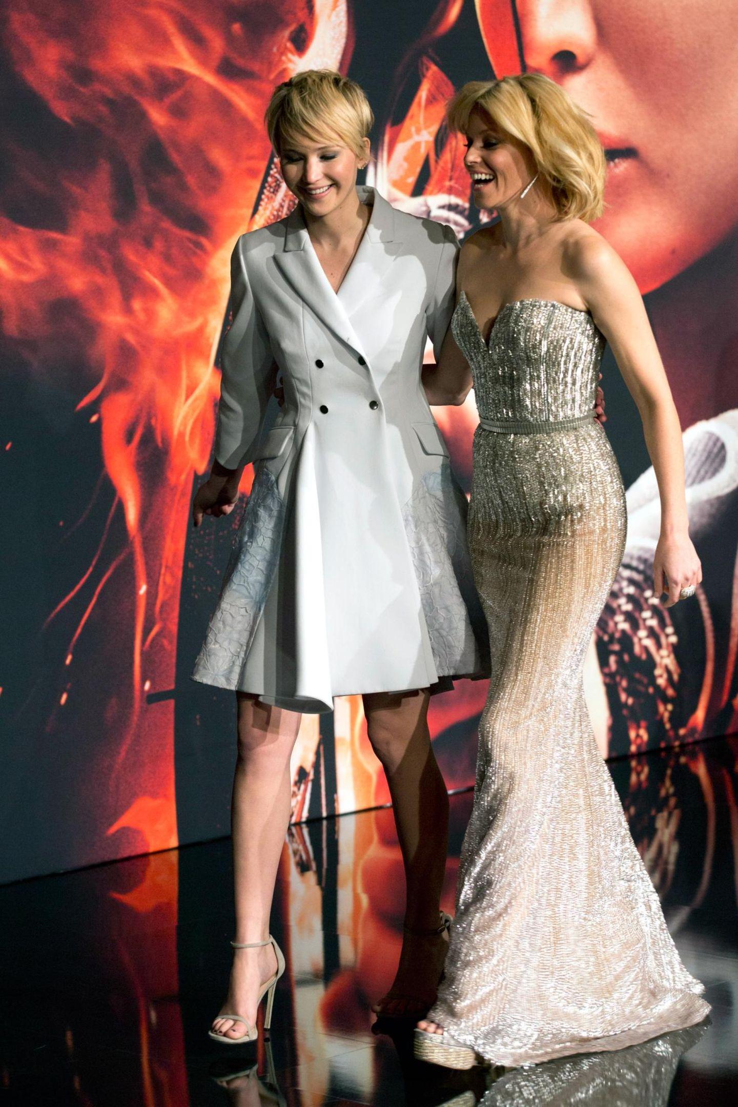 """Frauenpower: Arm in Arm schreiten Jenifer Lawrence und Elizabeth Banks zur Filmvorführung con """"Catching Fire"""" im Cinema Cinestar am Potsdamer Platz."""