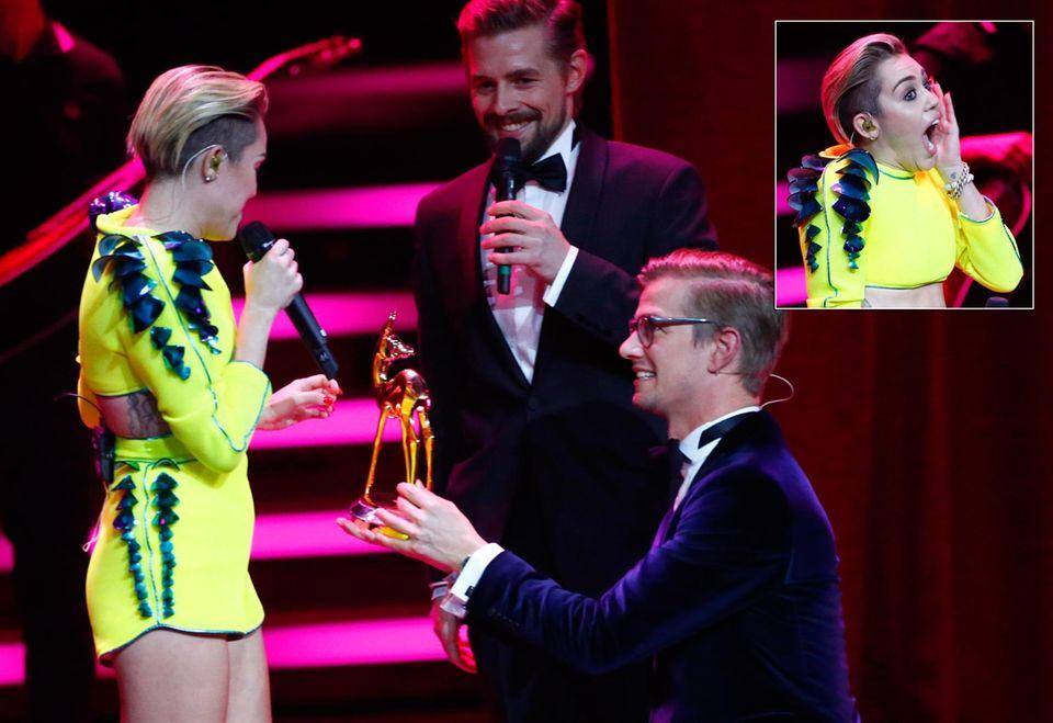 Joko Winterscheidt geht vor Miley Cyrus in die Knie, um ihr den Bambi zu übergeben. Klaas Heufer-Umlauf freut sich.