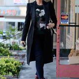 Der elegant geschnittene, schwarze Wollmantel steht im schönen Kontrast mit Gwen Stefanis Camouflage-Pullover. Und auf ihre weinroten, hohen Lieblings-Boots mag sie auch nicht verzichten.