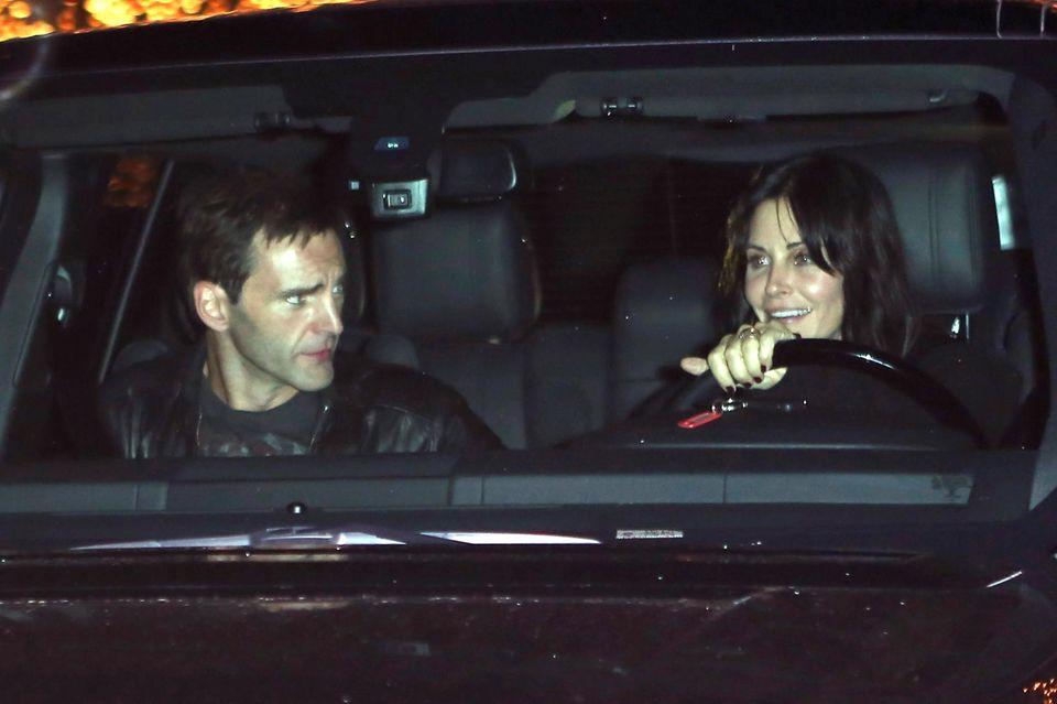 """Jedes Jahr Anfang Dezember gibt Jennifer Aniston ihre private """"Holiday Party"""". Dieses Mal fuhren wieder einige Stars vor, hier zum Beispiel Anistons gute Freundin Courteney Cox mit dem Musiker Johnny McDaid. Er kommt aus Nordirland und spielt in der Band """"Snow Patrol"""" Gitarre und Klavier."""