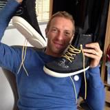 Coldplay-Sänger Chris Martin trennt sich von seinen Wildleder-Boots mit weißer Sohle und gelben Schnürsenkel.