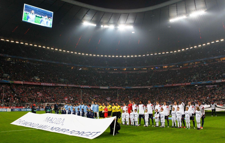 """Auch die Champions League erinnert an Nelson Mandela. Vor dem Spiel Bayern München gegen Manchester City in München stehen die Fußballer hinter einem Banner mit den Worten: """"Madiba, die Welt wird niemals vergessen""""."""