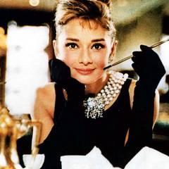 """Platz 1:  Audrey Hepburn als Holly Golightly in """"Frühstück bei Tiffany's"""". Basierend auf dem Buch von Truman Capote wurde der Film aus dem Jahr 1961 zum Klassiker - und mit ihr der Look der Hauptdarstellerin. Das Styling mit mehrreihigen Perlenketten, dem kleinen Schwarzen und extravaganten Hochsteckfrisuren wird noch heute oft und gerne kopiert."""