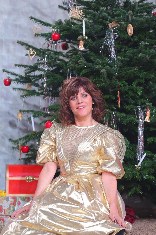 Für die RTL-Jubiläumsshow ließ sich Birgit Schrowange umstylen. Danach sah sie so aus wie auf dem Foto von vor 30 Jahren, das sie in im Goldkleid vor einem Weihnachtsbaum zeigt.