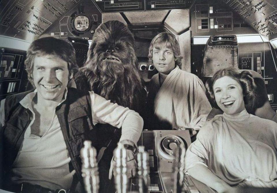 """Harrison Ford als """"Han Solo"""", Peter Mayhew als """"Chewbacca"""", Mark Hamill als """"Luke Skywalker"""" und Carrie Fisher als """"Prinzessin Leia"""" (von links nach rechts) bei Dreharbeiten im Cockpit. """"Ich habe das größte Lächeln von allen im Gesicht. Wirklich"""", schreibt Mayhew zu dem Foto."""