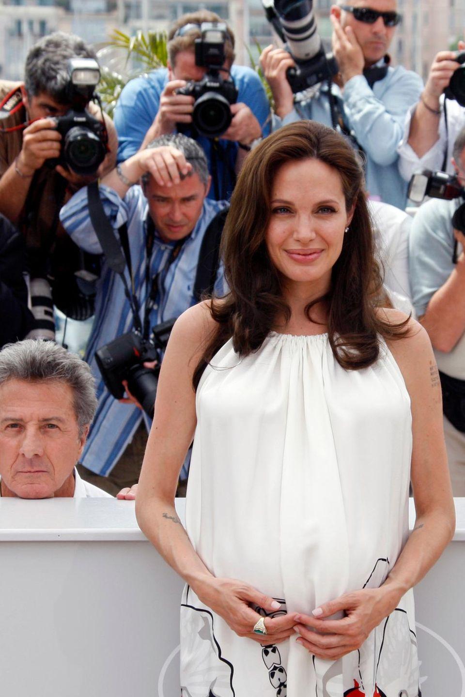 """Beim """"Cannes Film Festival"""" machen Jack Black und Dustin Hoffman Faxen hinter Angelina Jolie - die Fotografen freut es."""