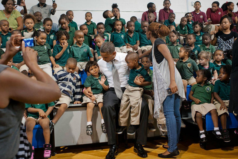 """Während seines Wahlkampfs posiert Barack Obama für ein Foto mit Schülern. Doch ein Junge hat scheinbar andere Interessen als den Besuch des Präsidenten zu verfolgen, im Hintergrund sieht man, wie er ein Mädchen küsst. Obama postet dazu auf seinem Twitter-Account: """"Check out the kids in the back row to see why this is one of our favorite photos from this year."""""""