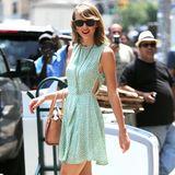 Taylor Swift zeigt, dass sich Pastellfarben wie das zarte Mintgrün ihres kurzen Pünktchenkleids auch gut mit knalligem Pink kombinieren lassen.