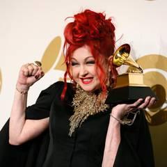 Cyndi Lauper posiert mit ihrem Preis in Siegerpose für die Fotografen.