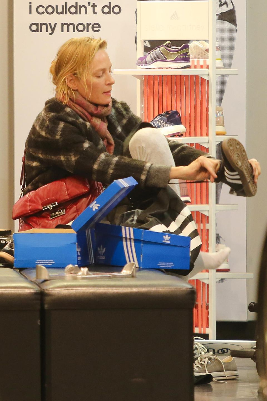 5. Oktober 2014: Uma Thurman probiert in einem Schuhladen in SoHo, New York, Sneaker an.