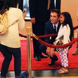 12. Juni 2014: Robert Pattinson macht posiert auf dem roten Teppich für ein Foto mit einem kleinen Fan.