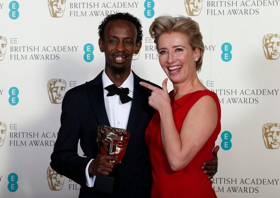"""Emma Thompson scherzt mit Barkhad Abdi. Der Schauspieler hat den """"BAFTA""""-Award als bester Nebendarsteller in """"Captain Phillips"""" bekommen."""