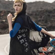 Das schwarze, doppellagige Kapuzenkleid mit Schriftzug auf dem Rücken, von Y-3 freut sich über Farbtupfer wie den blauen Lochstrick-Cardigan, von Schumacher und die gelben Running Tights, von Adidas by Stella McCartney. Sneaker von Ash
