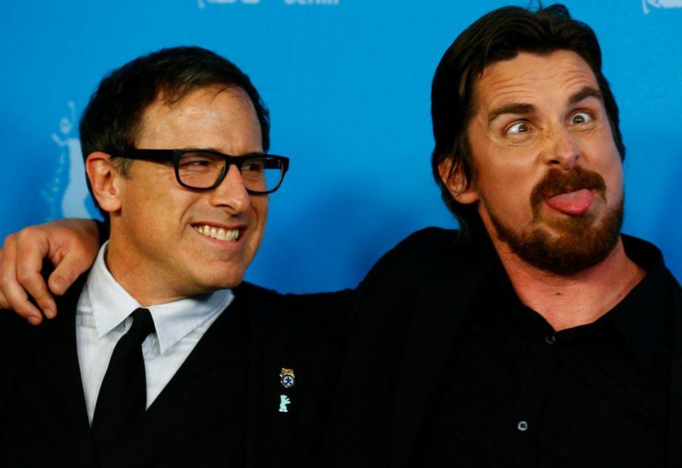 """Christian Bale ist gut drauf und schneidet Grimassen. """"American Hustle""""-Regisseur David O. Russell sagt, er gehe nie mit großen Erwartungen an einen Film ran. Viele seiner Helden wie zum Beispiel Gene Hackman haben keinen Oscar gewonnen. Aber man weiß nie, was passiert, deshalb ist er gelassen, was den Oscar angeht."""