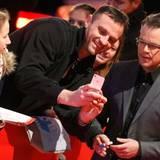 Matt Damon lässt sich das Smartphone eines Fans zeigen.