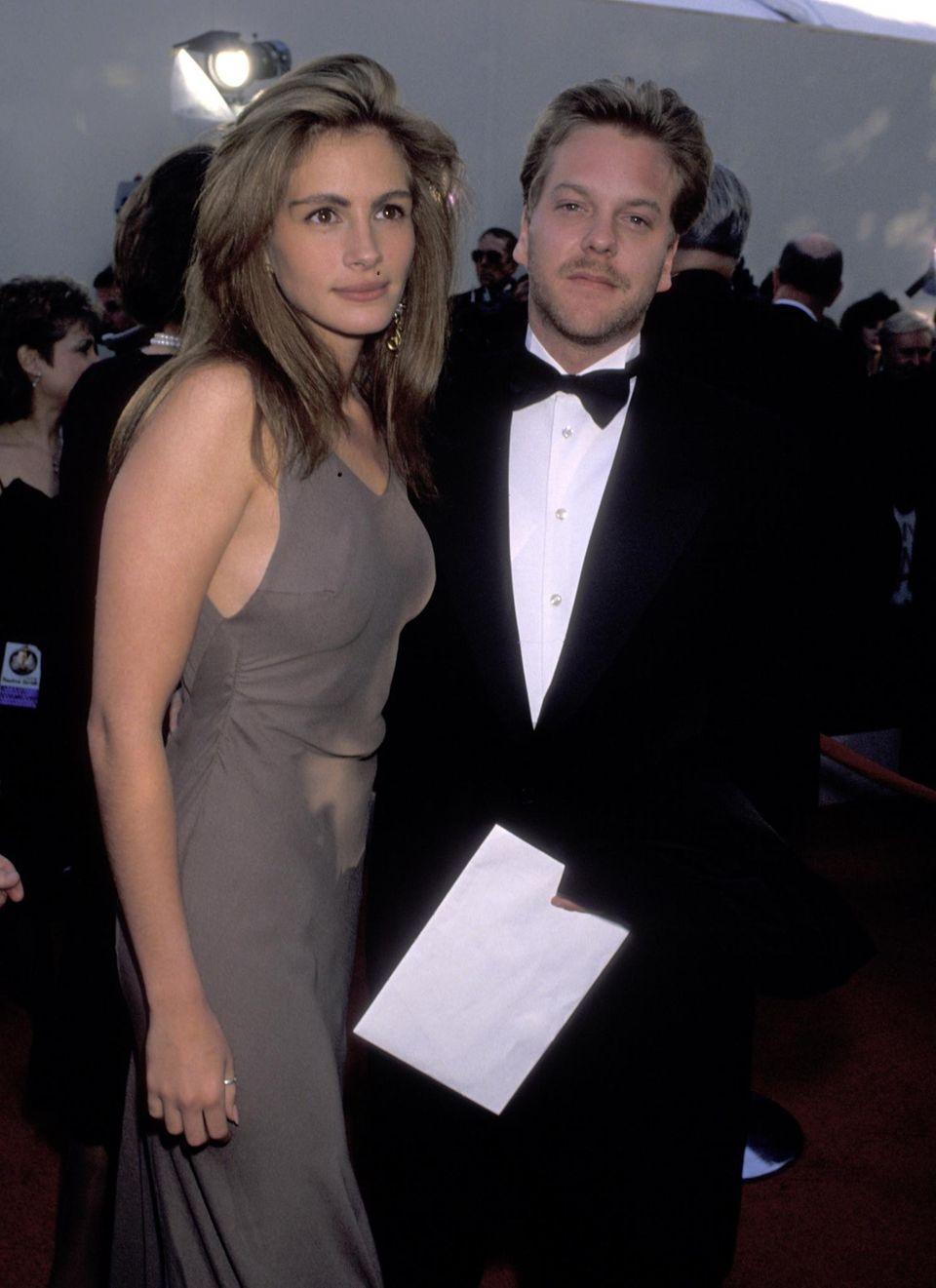 """1990:  Julia Roberts kommt zu ihrem ersten Oscar-Auftritt mit ihrem damaligen Freund Kiefer Sutherland (den sie etwa anderthalb Jahre später nur wenige Tage vor der geplanten Hochzeit verlässt). Die 22-Jährige ist als beste Hauptdarstellerin in """"Magnolien aus Stahl"""" nominiert. Ein Jahr später kann sie sich ein weiteres Mal über eine Nominierung freuen, diesmal für """"Pretty Woman"""". Die Trophäe kann sie aber erst 2001 mit nach Hause nehmen, für ihre darstellerische Leistung in """"Erin Brokovich"""". Auch 2014 kann sie sich Hoffnungen auf einen Oscar machen, als beste Nebendarstellerin ist sie mit """"August: Osage County"""" nominiert."""