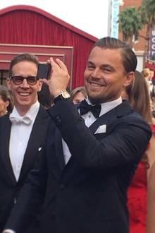 Leonardo DiCaprio fotografiert Fans und Reporter vom roten Teppich aus.