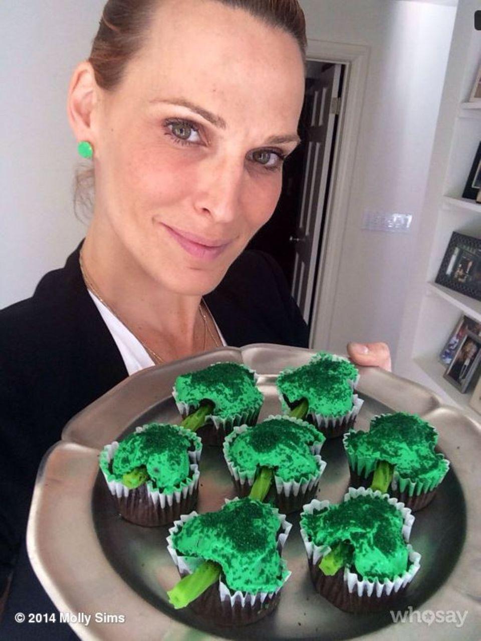 Molly Sims posiert mit grünen Ohrringen und Cupcakes in Kleeblatt-Form für ein Foto.