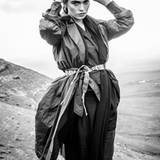 Tannengrüner Trenchcoat aus Fallschirmseide über einer nachtblauen Bluse. Dazu eine Wildlederhose in Dunkelgrau. Alles von Hermès. Ringe von Thomas Sabo. Gürtel und Mütze vintage