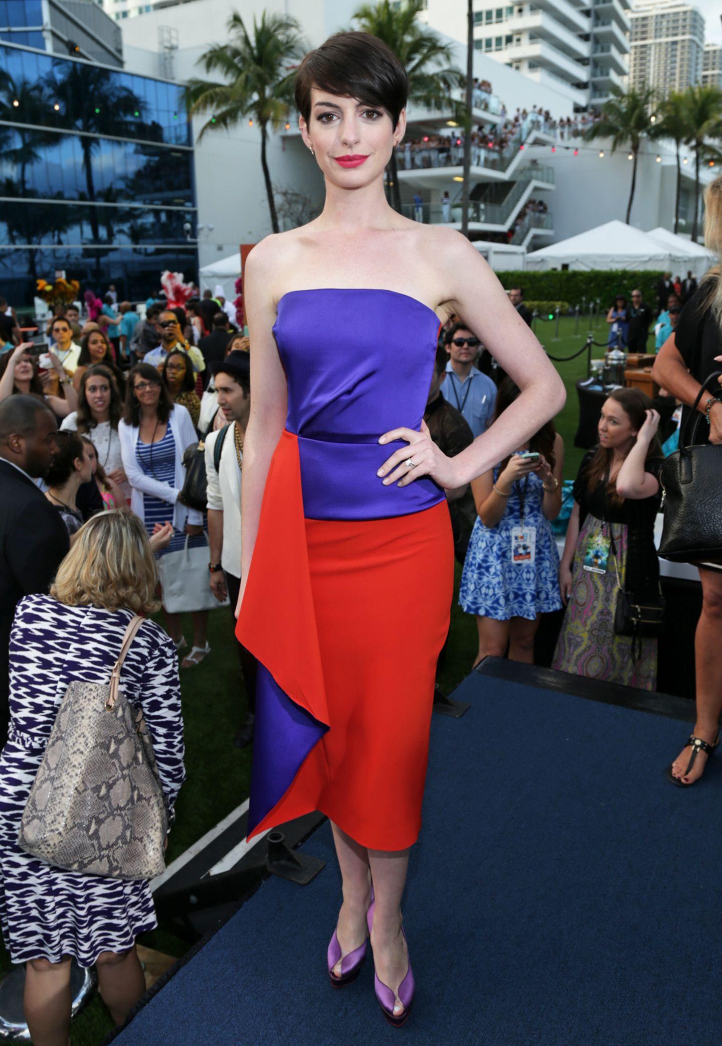 In einem aufregenden Bandeaukleid von Designerin Roksanda Ilincic strahlt Anne Hathaway auf einer Filmpremiere.