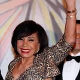 Sängerin Shirley Bassey winkt freudig, als sie ankommt.