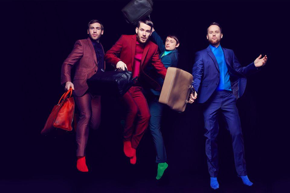 Von links: Niels Grötsch trägt ein Hemd von Emporio Armani, einen Anzug von Joop, orangefarbene Socken von Falke, einen orange-roten Shopper von Tods. Johannes Strate trägt ein Hemd von Emporio Armani, einen Anzug von Strellson, rote Socken von Burlington, eine schwarze Bowling Bag von Bottega Venetta. Jakob Sinn trägt ein Hemd von Emporio Armani, einen Anzug von Strellson grüne Socken von Burlington, eine grüne Bowling Bag von Bottega Venetta. Kristoffer Hünecke trägt ein Hemd von Emporio Armani, einen Anzug von Joop, blaue Socken von Falke, einen beigen Shopper von Louis Vuitton
