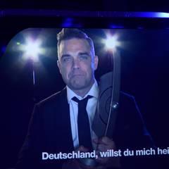 Robbie Williams kann zwar nicht vor Ort sein, liebt Deutschland aber trotzdem und will das Land sogar heiraten, sagt er zumindest.