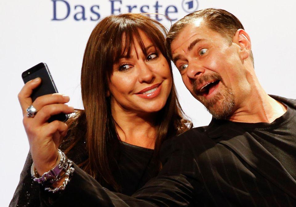 Die Schauspieler Simone Thomalla und Sven Martinek machen ein Selfie auf dem roten Teppich.