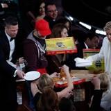 Auch Stars sind hungrid: Ellen DeGeneres hat für alle Anwesenden insgesamt drei große Pizzas bestellt und Brad Pitt hilft ihr beim Verteilen.