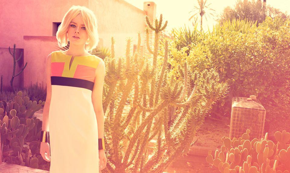 Ein typisches Beispiel für den Look ist das ärmellose Kleid in leicht ausgestellter A-Linie. Es hat einen flachen, runden Ausschnitt mit Schlitz und dekorative Farbflächen am Oberteil. Von Basler. Armreifen von Michael Kors