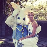 Heidi Klum nimmt auf dem Schoß des Osterhasen Platz.
