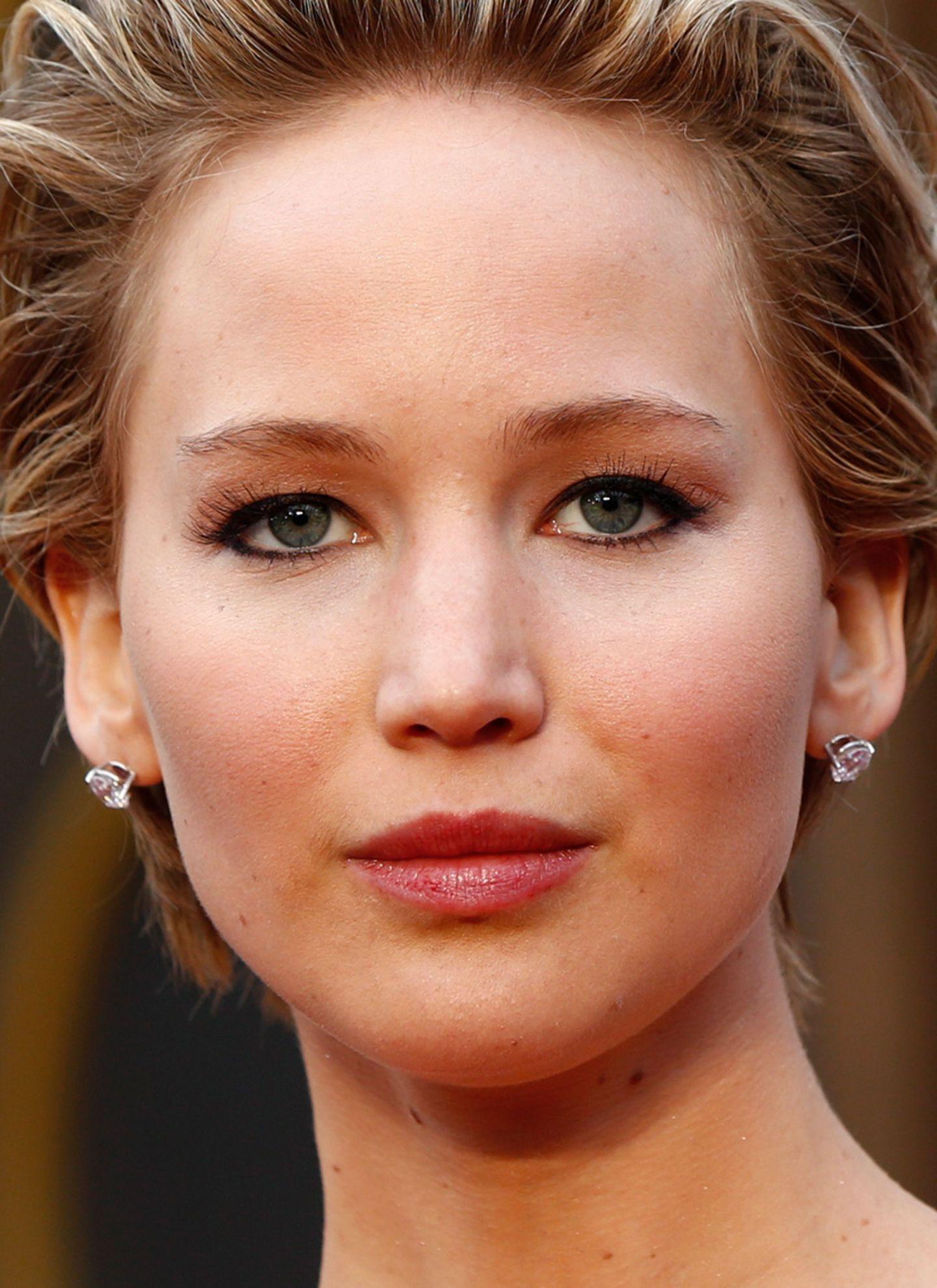 Kunstwimpern und ein sehr zurückhaltendes Make-up lenken den Blick auf Jennifers Kurzhaarfrisur, die sie toupiert und nach hinten frisiert trägt.