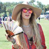 Vanessa Hudgens trägt eine trendy Sonnenbrille und fächert sich gegen die Hitze Luft zu.