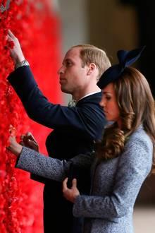 William und Catherine behängen eine Wand mit Mohnblüten.