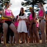 Am Strand von Manly ist Herzogin Catherine umringt von jungen Rettungsschwimmerinnen mit denen sie sich gut gelaunt unterhält.