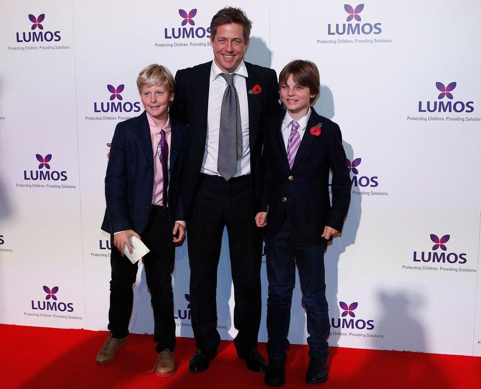 Selbst hat Hugh Grant keine Kinder mit seiner Langzeitliebe Liz Hurley. Doch er lässt sich nicht lange bitten, als sie ihn fragt, ob er der Patenonkel ihres Sohnes Damien (rechts im Bild) wird.