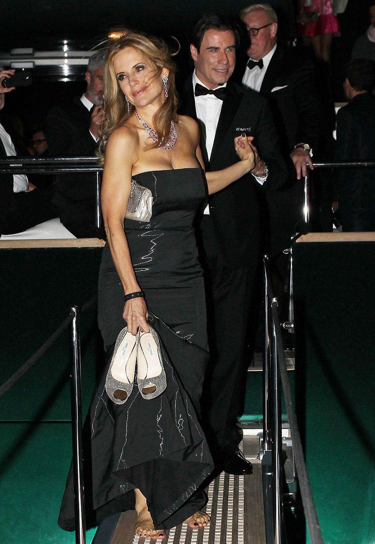 John Travolta ist ganz Gentleman und hilft seiner barfüßigen Frau Kelly Preston vom Boot herunter.