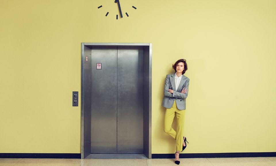 """Oben klassisch grau, unten sonnig gelb – ein easy Mix zum Nachmachen: Doppelreiher und Seidenbluse mit kleinem Rundkragen, beides von Emporio Armani. Schmale Bügelfaltenhose in der Farbe """"Lime"""", von Basler. Silberring von Hermès, schwarze Slingbacks von Dior"""