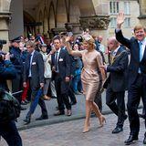 Zu Fuß geht es durch eine Straße in Münster, die gesäumt ist von Fahnen schwenkenden Fans, die dem Königspaar zuwinken.