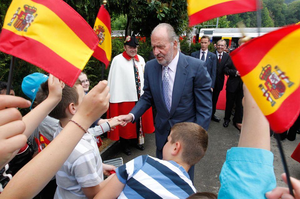 Mai 2011  Juan Carlos zeigt sich volksnah und schüttelt bei einem Schweizbesuch Kinderhände.
