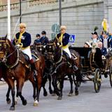 Königin Silvia, jetzt in Nationaltracht, und König Carl Gustaf fahren per Kutsche durch Stockholm. Mit ihren fährt Prinz Carl Philip (verdeckt).