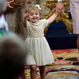 Prinzessin Estelle scheint, als sie an der Hand von Prinzessin Victoria die Kirche verlässt, etwas Spannendes entdeckt zu haben.