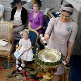 """Prinzessin Victoria, als eine der Patinnen, gießt das Taufwasser ins Taufbecken. Es stammt aus einer Quelle in Öland, wo die Königsfamilie ihre Sommerresidenz hat. Prinzessin Estelle schaut ihrer Mutter dabei fasziniert zu.  Victoria trägt ein Kleid aus dem Hause """"Dolce&Gabana""""."""