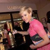 """Wolke Hegenbarth signiert eine """"Moët & Chandon Champagner"""". Die Marke ist Mitsponsor der Jubiläumsfeier."""