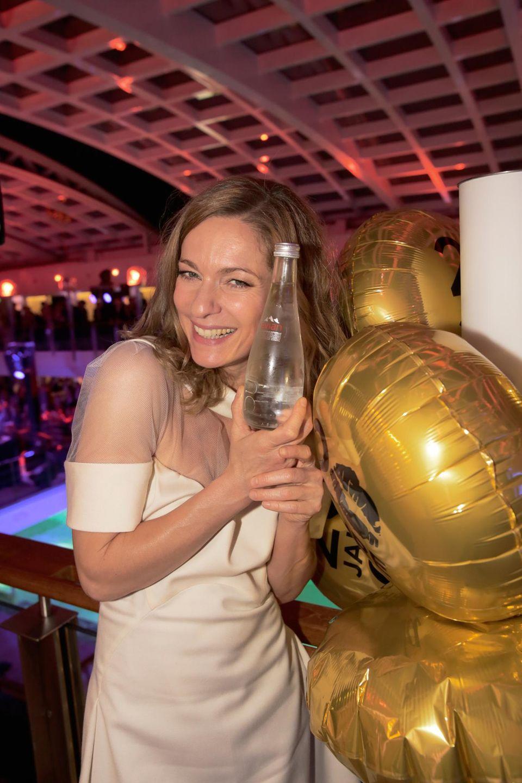 """Lisa Martinek kühlt sich auf der Party die Hände an einer kühlen Flasche Wasser von Sponsor """"Evian""""."""