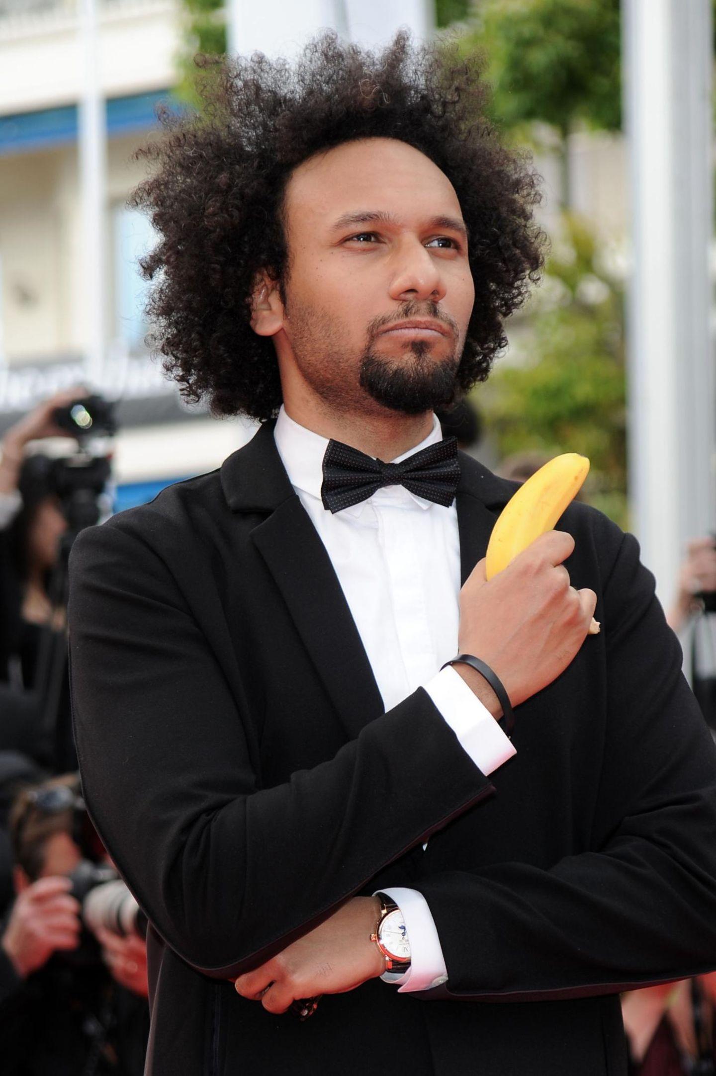 Schauspieler Yassine Azzouz bringt sich auf dem roten Teppich der Eröffnungsgala mit Banane und James-Bond-Pose ins Gespräch.
